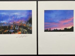 Two cityscape photographs on separate pieces of paper. They are both signed below in ink.