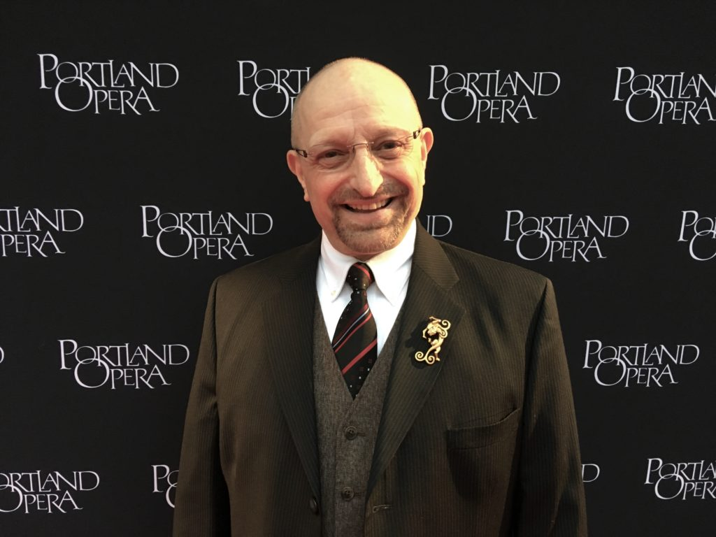 """A man in a suit smiles at the viewer and stands against a background that says """"Portland Opera."""""""