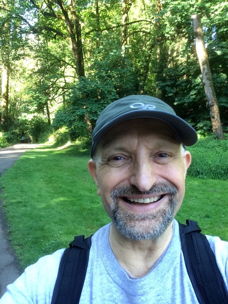 A man wearing a cap smiles at the viewer. He is in nature.
