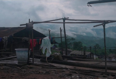 Wooden poles creating a structure with clothes hanging on it. Clouds and mountains are seen in the background.