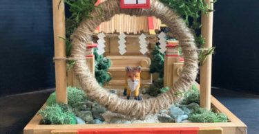 A set made of wood, foliage, twine, with a small fox in the center.