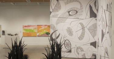 A gallery space with an organically patterned wall, paintings, and a sculpture with foliage in the center of the room.