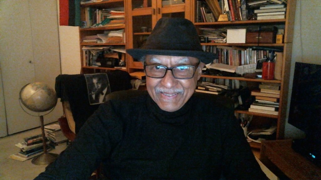 A man in a background with books, wears a hat and smiles at the viewer.