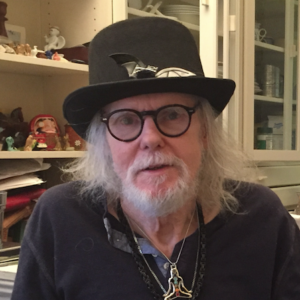 head shot of Ed McCormack wearing a black top hat, round glasses in his kitchen