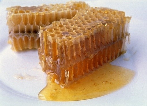 honeycomb on a plate , oozing with honey