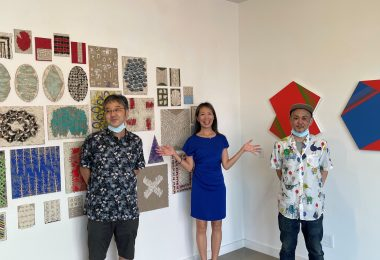 3 Japanese artists standing in front of their artwork in a gallery