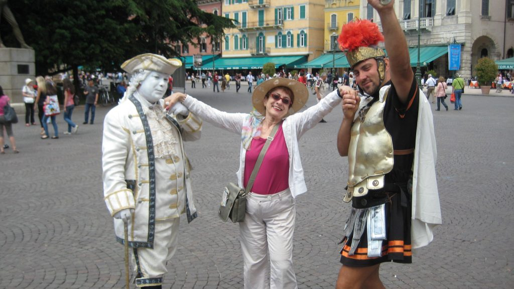 photograph of the author with two people in costumes - on the left a statue like nobility and on the right a roman centurion, taken in a pedestrianized plaza.