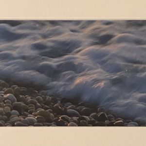 color photograph of foaming waves on a pebble beach
