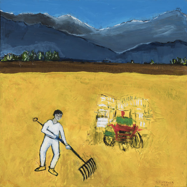 a farmer is racking the golden fields with a hay cart in the center and blue mountains in the background