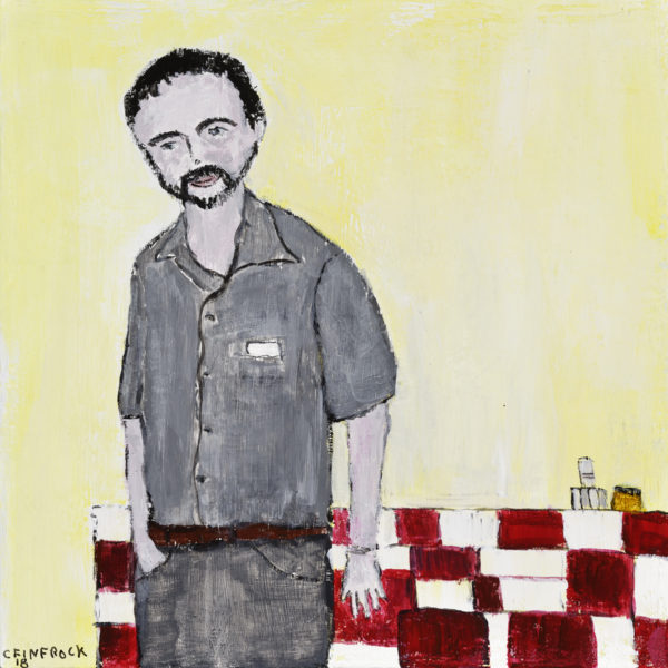 man in a grey shirt and pants by a checkered red table and yellow walls