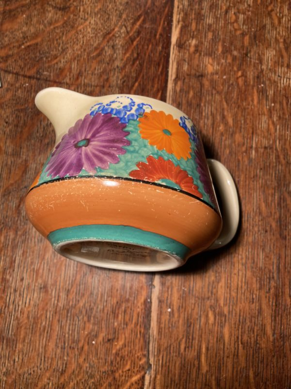 round squat jug on its side with bright daisy like flowers on a green grass packground - jug is on a wooden floor.