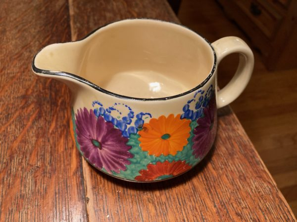 round squat jug with a handle and bright daisy like flowers on a green grass packground - jug is on a wooden floor.